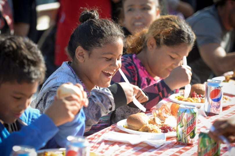 Erica Moore, 9, and her sister April Moore, 11, enjoy a Thanksgiving meal with all the trimmings at the Hope of the Valley Shelter in Van Nuys Wednesday. The shelter fed over 1,000 homeless and also held a street fair and gave away two cars.    (Photo by David Crane, Los Angeles Daily News/SCNG)